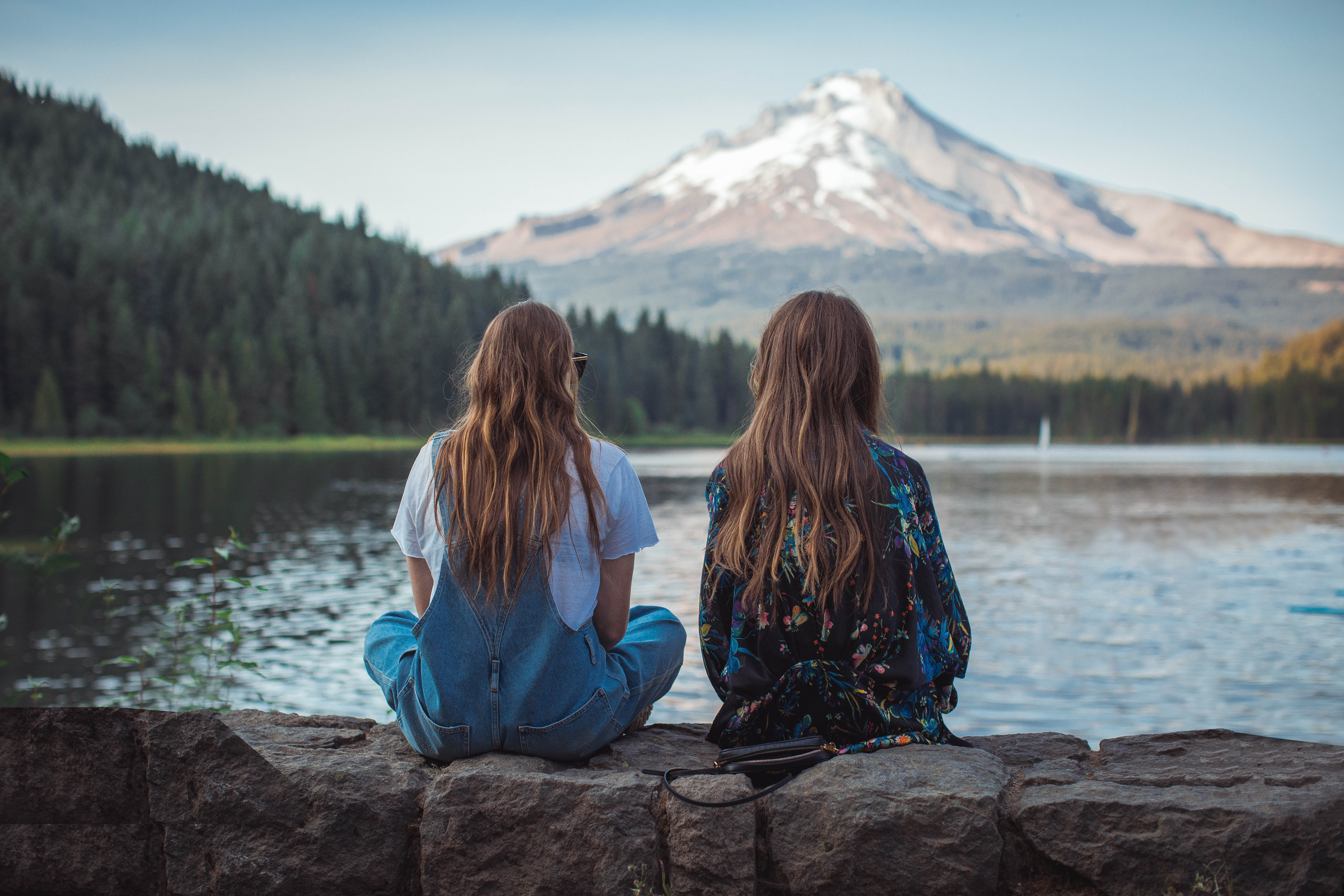 2 girls sitting by a lake looking at a mountain