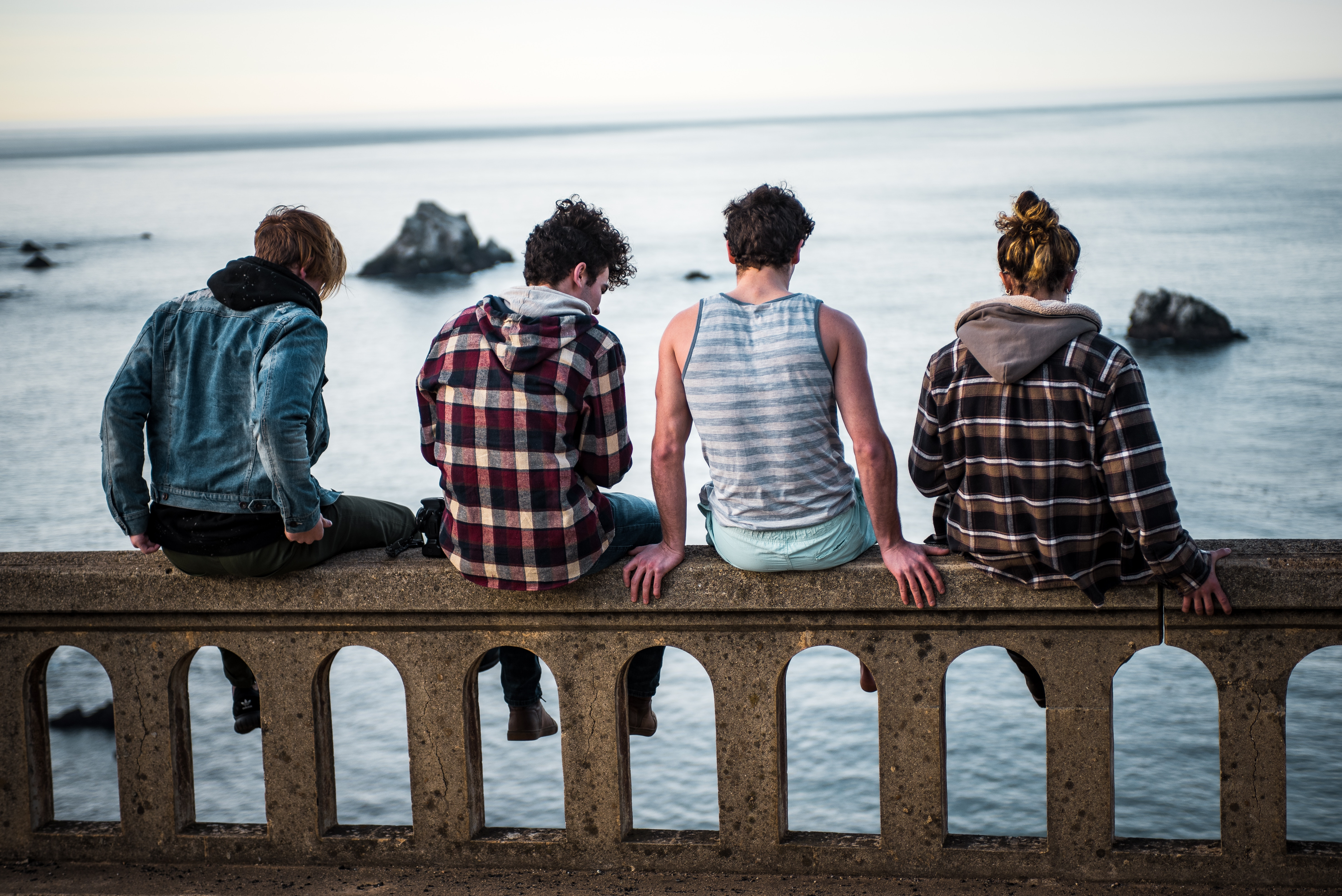 4 people sitting on a fence