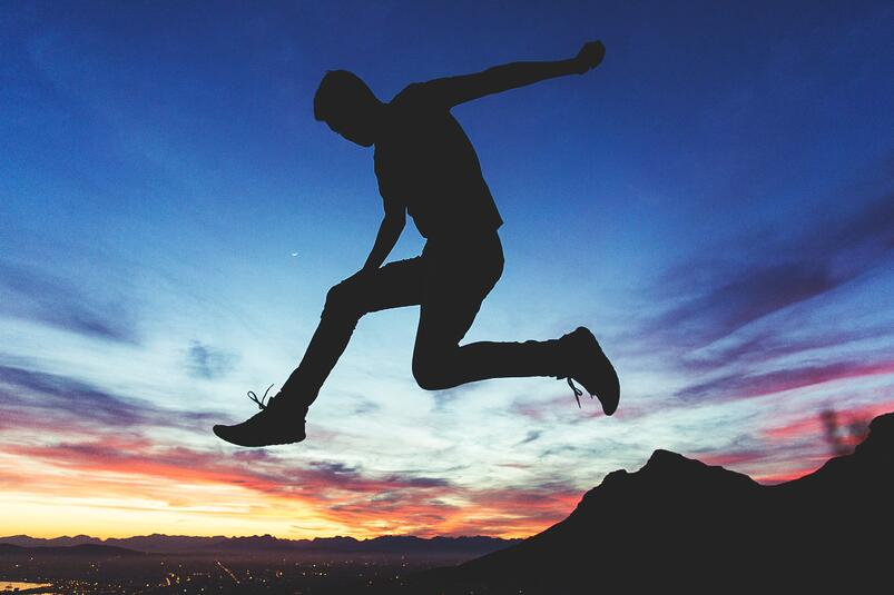Man jumping at dawn with colorful sky.jpg
