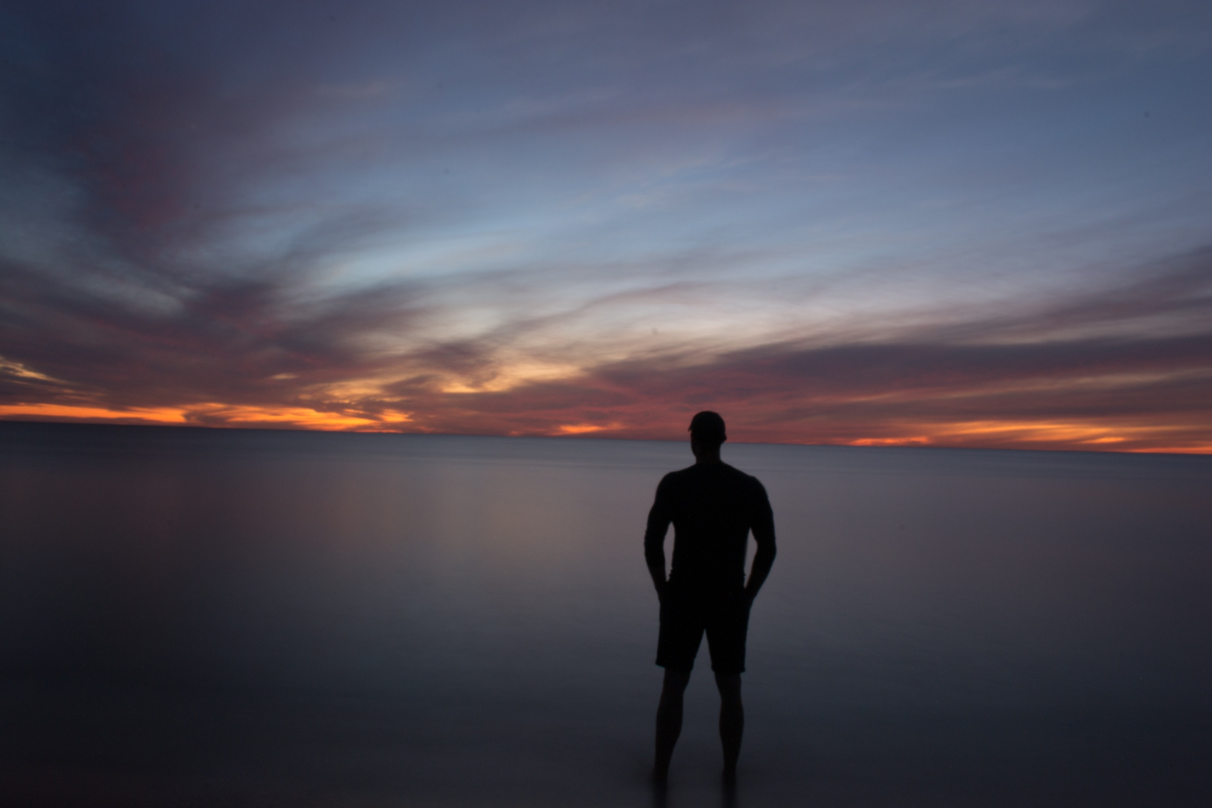 man standing in calm waters