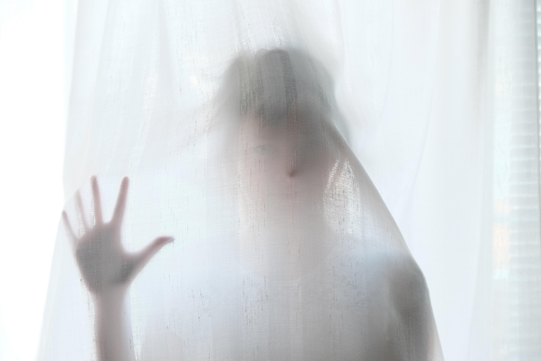 woman behind screen looks like a ghost