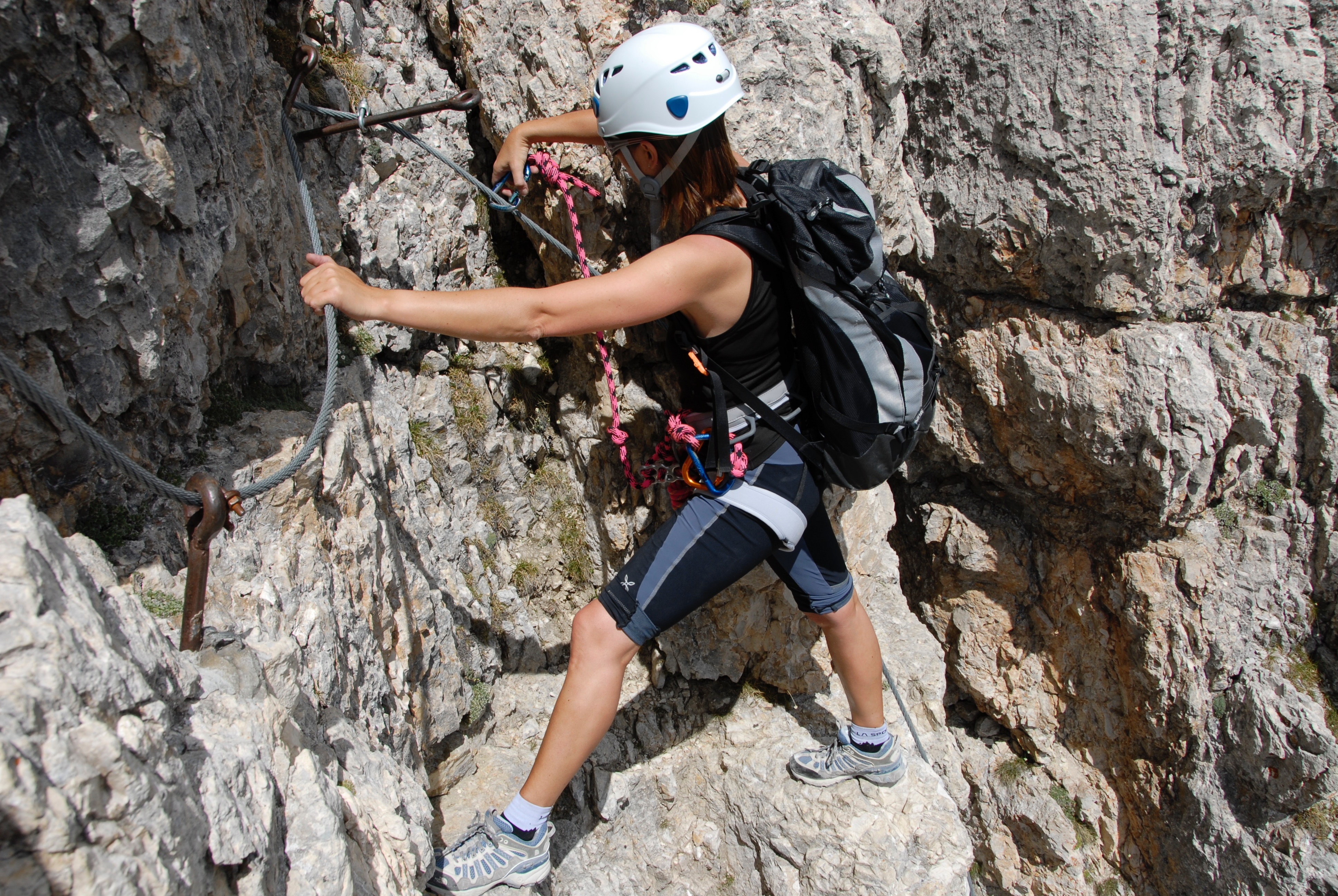 woman climbing steep cliff
