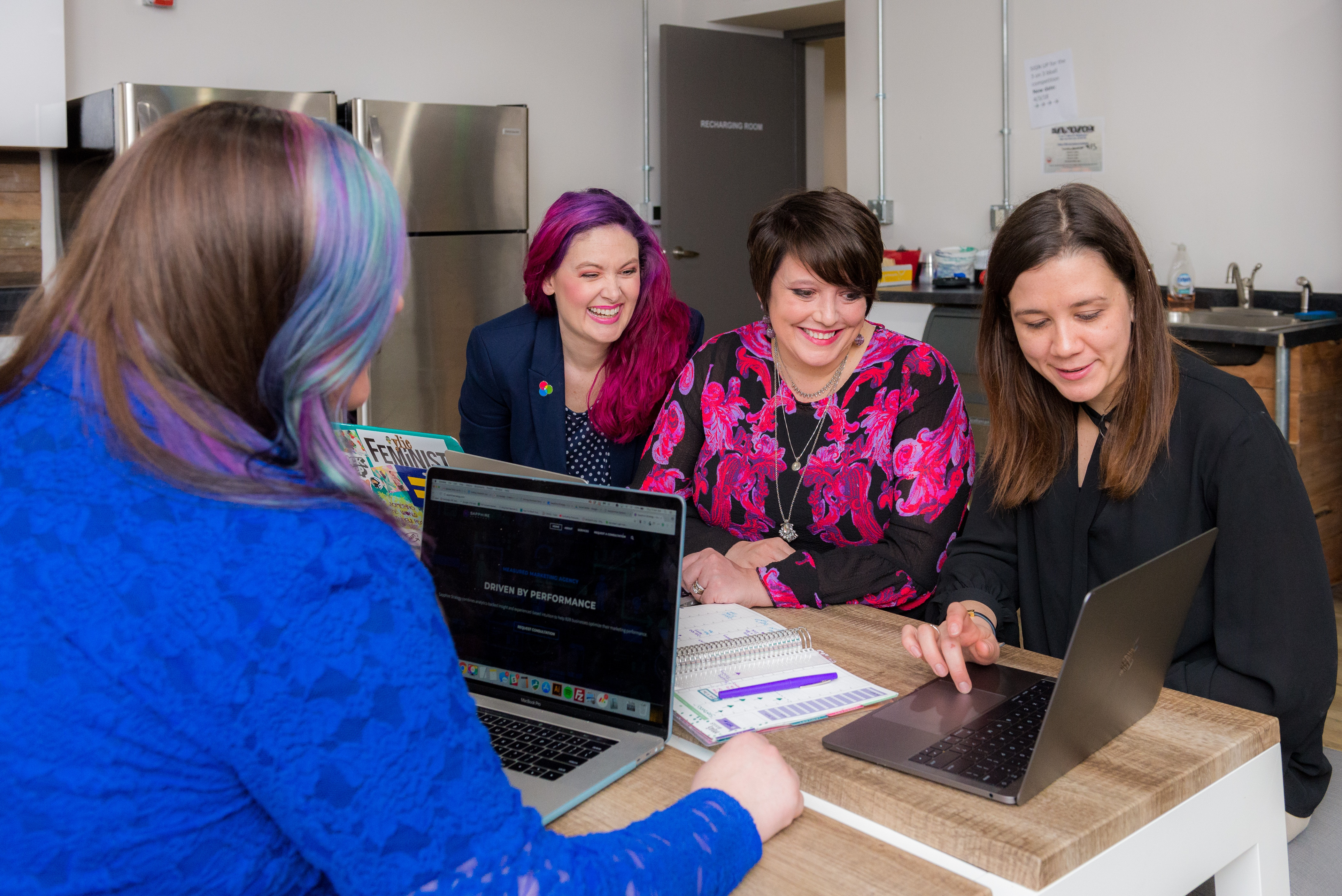 women in an office on laptops